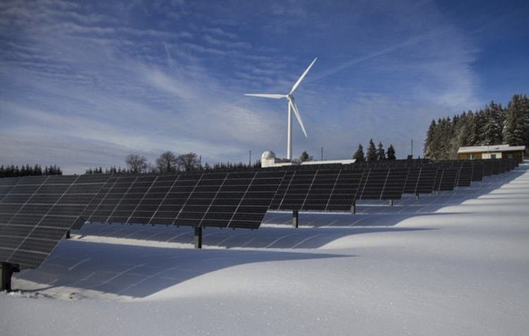 Solar panels and windmill in snow